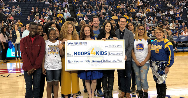 L to R holding the check: Rachel Wyley (Playworks), Joanne Pasternack (Warriors Community Foundation), Sean Taube (Taube Philanthropies), Stephanie Isaacson (PG&E), and Kyle Marinshaw (Koret Foundation); together with other beneficiaries.